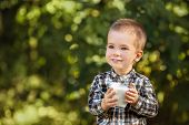 Little Boy Drinking Yogurt From Glass Outdoors. Portrait Of Child With Funny Milk Mustache poster