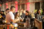 Defocused People At The Event Standing Near The Bar And Barman. Blurred Indoor Event Background. poster