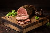 Juicy Roast Beef With Spices Sliced On A Cutting Board, Delicious Meat, Traditional Food. On Dark Ba poster