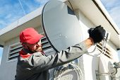 Service worker installing and fitting satellite antenna dish for cable TV poster