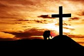stock photo of cross hill  - Dramatic sky scenery with a mountain cross and a man seating hopelessly under the cross - JPG