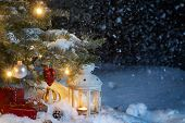 Christmas Composition - Gifts And A Lantern In The Snow Under A Christmas Tree Decorated With Lights poster