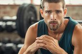 Young muscular man resting in gym while looking at camera. Portrait of competitive sportsman at well poster