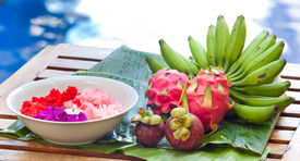 stock photo of crown green bowls  - Display of tropical fruit on banana leaf on wooden table in natural light - JPG
