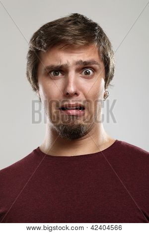 Portrait of young man with scared expression  isolated over background