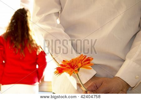 Man hiding flower and woman looking out the window