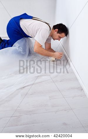 Worker Laying Protection Film Before Painting