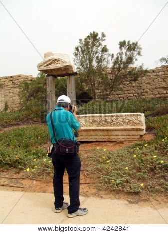 Tourist Taking Photo Of Ruined Stone, Caesarea, Israel
