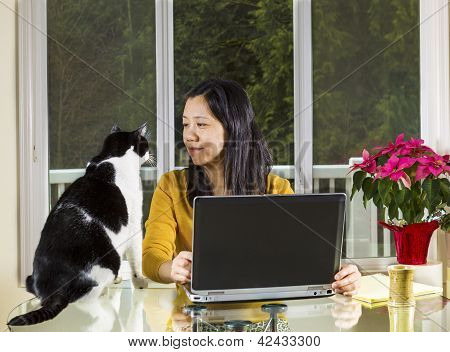 Mature Woman Working At Home Wth Family Looking At Her