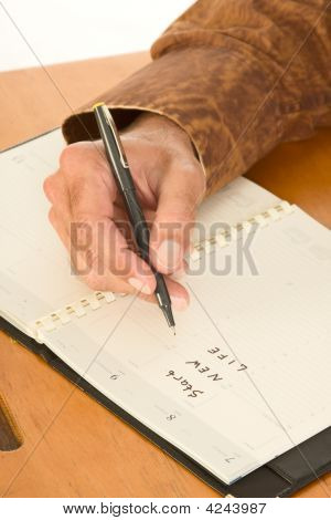 Hand Of Man Writing In Day Planner About New Life