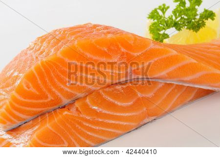 two fresh salmon steaks with lemon and parsley