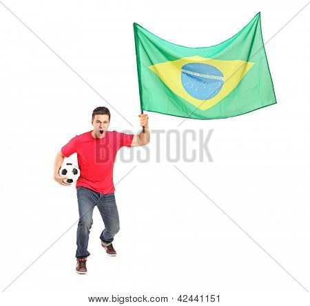 Full length portrait of an euphoric fan holding a ball and flag of brazil isolated on white background