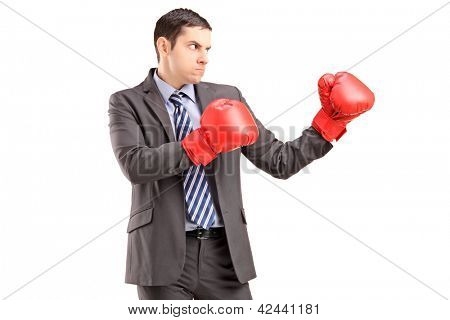 Angry man in suit with red boxing gloves ready to fight isolated on white background