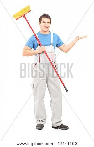 Full length portrait of a cleaner in a uniform with a broom pointing with his arm isolated on white background