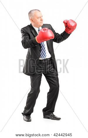 Full length portrait of a mature businessman with red boxing gloves ready to fight isolated on white background