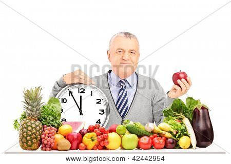 Mature man with red apple, clock and fruit and vegetables on a table isolated on white background