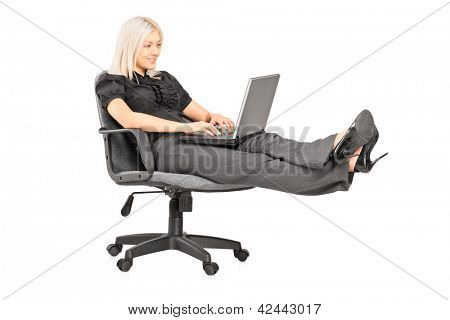 Young woman sitting on office chair with her legs up and working on a laptop isolated on white background