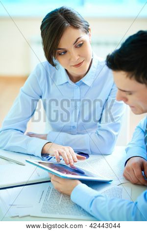 Image of businesswoman showing something to her partner on touchpad