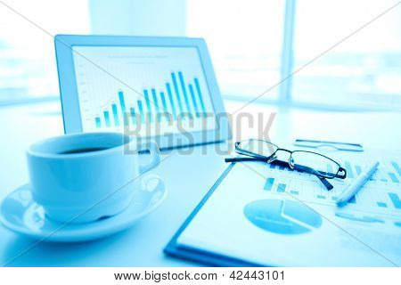 Image of an office workplace with paper, touchpad and a cup of coffee