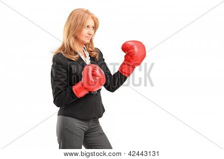 A mature businesswoman with red boxing gloves ready to fight isolated on white background