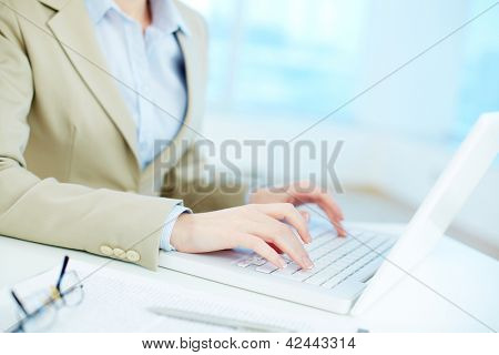 Close-up of white collar worker typing on laptop