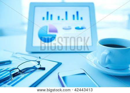 Image of an office workplace with paper, wireless gadgets and a cup of coffee