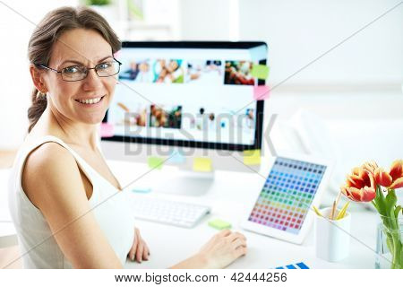 Portrait of happy female designer looking at camera at workplace