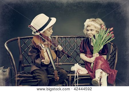 Cute little boy is playing the violin to the charming little lady. Retro style.
