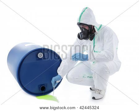 Man wearing protective suit and respirator sampling dangerous chemical liquid leaking from blue container