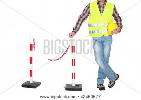 Traffic guard standing beside a barrier
