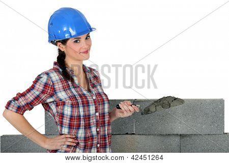 female mason applying cement