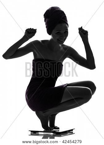 one beautiful asian young woman  happy on   weight scale in silhouette studio isolated on white background