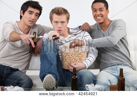 Três amigos homens assistindo televisão juntos