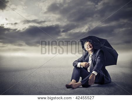 businessman sitting on the ground in the desert with umbrella