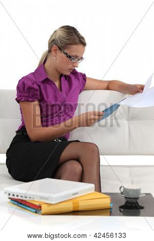 Blond businesswoman sat on a sofa reading through document