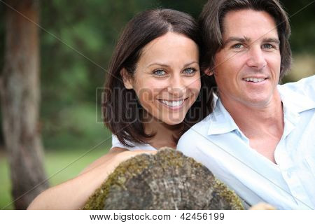 Couple leaning on tree trunk