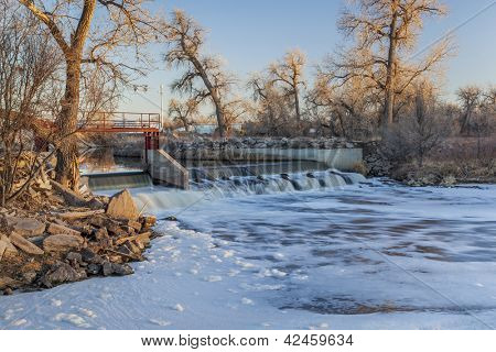 small river dam diverting water to farmland irrigation - South Platte River near Fort Lupton, Colorado, winter scenery at sunset