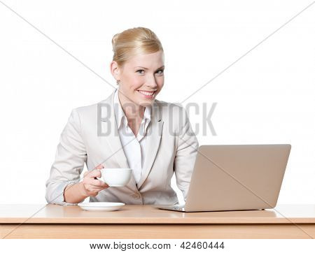 Young businesswoman sitting at a table with a cup of tea, isolated