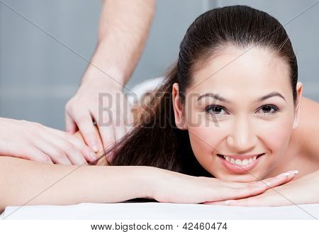 Smiling woman during luxurious procedure of massage at spa salon