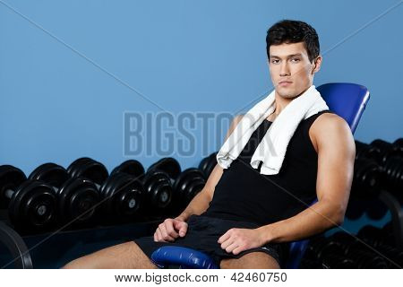 Athletic man rests sitting on blue simulator in gym class