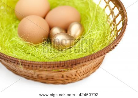 Brown and golden easter eggs are in wattled basket with sisal green fibre, isolated on white