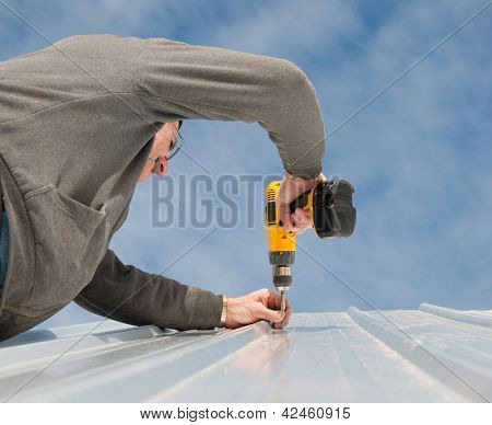Man fastening down a metal roof with screws; with cloudy sky background