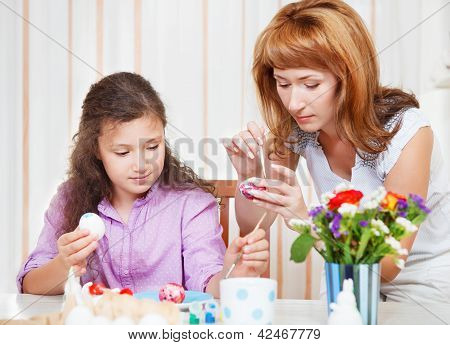 Mother And Her Little Daughter Painting On Easter Eggs