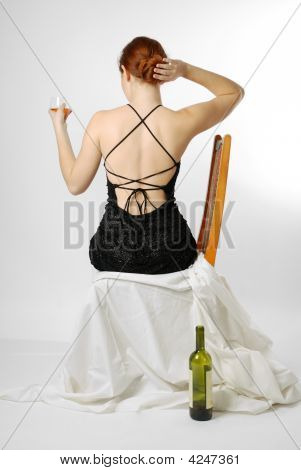 Young Woman Sitting With Wineglass, Rear View