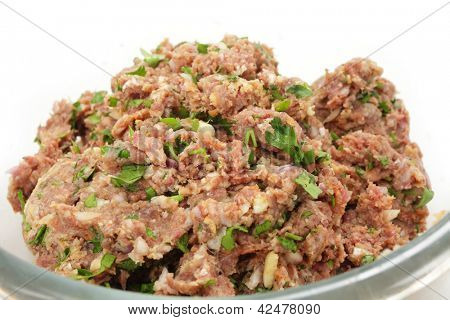 A glass bowl full of a mixture of minced beef, onion and breadcrumbs, with chopped parsley, garlic and spices ready for forming into homemade beefburgers.