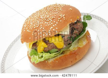 A homemade beefburger patty in a sesame seed bun, with lettuce, arugula (rocket), mustard and a slice of cheese