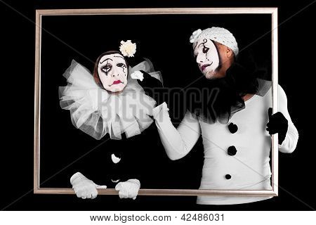 Two Clowns In A Frame, One Looks Sorrowful