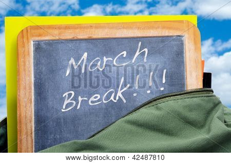 march break written in a blackboard in a school bag with books