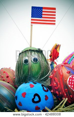 a pile of easter eggs painted in different colors and patterns, one of them with long hair and eyes, and the american flag