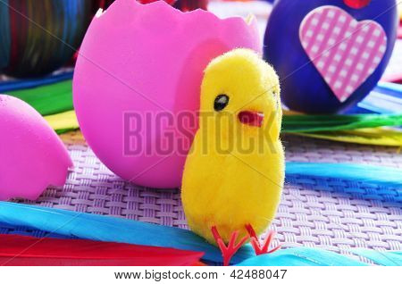 some easter eggs painted in different colors and patterns, one of them broken and a teddy chick